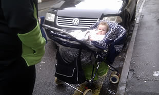 A baby in a pushchair, forced onto the road