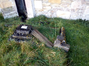 Broken stone cross in Templecombe church graveyard, resulting from theft of roof lead