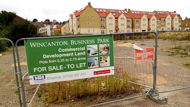 A plot of commerical land up for sale/let, with the New Barns residential development in the background
