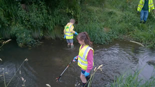 Kids in the river with litter-pickers