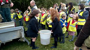 Girls from King Arthur's school carry the bucket to the river bank