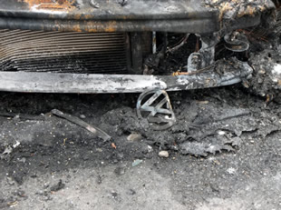 A burnt VW badge lying in the embers