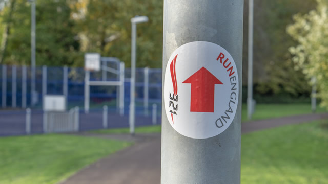 A directional sticker on a post near the Cale Park MUGA, at the turning point of the 1km route