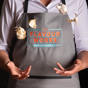 Someone wearing a Flavourworks apron, juggling cloves of garlic