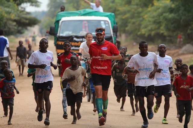 Brendan Rendall running in Malawi with local children