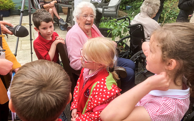 Pupils from Our Lady of Mount Carmel Primary School with residents of Carrington House, Wincanton, talking to BBC Somerset