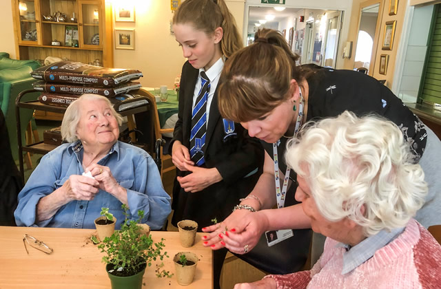 A King Arthur's student potting plants with a resident of Carrington House, Wincanton